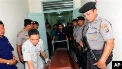 Cảnh sát vũ trang Indonesia đứng gác bên cạnh một quan tài của một trong các nghi can khủng bố tại bệnh viện ở Denpasar, Bali, ngày 19/3/2012
