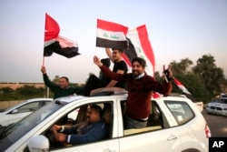 Iraqis wave national flags, celebrating the anniversary of the victory over the Islamic State group, in the so-called Green Zone in Baghdad, Iraq, Monday, Dec. 10, 2018. (AP Photo/Karim Kadim)