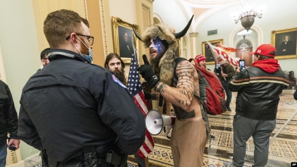 """资料照片:来自亚利桑那州的""""Q匿名萨满""""钱斯利在国会大厦与警察对峙。(2021年1月6日)(photo:VOA)"""