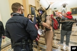 FILE - In this Jan. 6, 2021, file photo supporters of President Donald Trump are confronted by U.S. Capitol Police officers outside the Senate Chamber inside the Capitol in Washington. An Arizona man seen in photos and video of the mob wearing a fur hat w