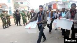 Para anggota komisi pemilihan umum membuang materi pemilu setelah mendengar berita kemungkinan serangan oleh pengunjuk rasa di Bogra (5/1).
