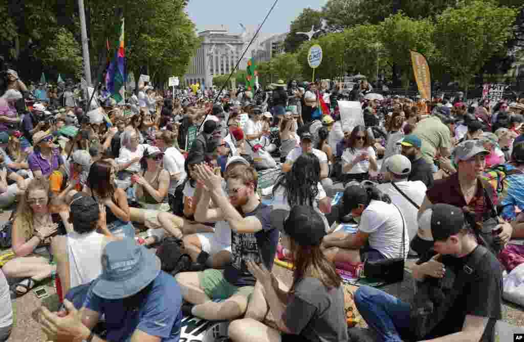 Los manifestantes se sientan en el suelo a lo largo de la avenida Pennsylvania en frente de la Casa Blanca en Washington durante la manifestación este 29 de abril de 2017.
