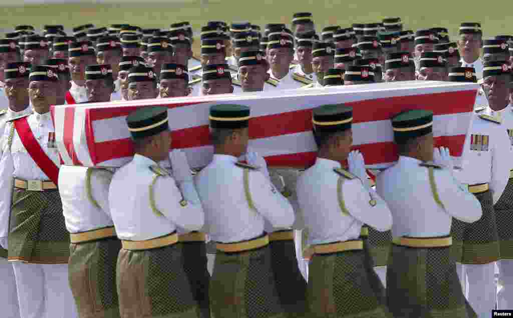 An honor guard stands by as the remains of a passenger of downed Malaysia Airlines MH17 is carried during a repatriation ceremony at KLIA airport in Sepang, Aug. 22, 2014.