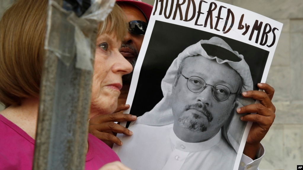 People hold signs during a protest at the Embassy of Saudi Arabia in Washington about the disappearance of Saudi journalist Jamal Khashoggi, Oct. 10, 2018.