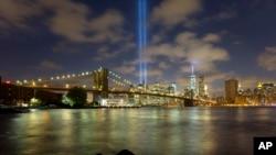 "Pancaran sinar biru terlihat memancar dari balik jembatan Brooklyn dan bangunan sekitar kompleks World Trade Center, New York (10/9). ""Tribute in Light"" ini dinyalakan untuk mengenang tragedi serangan teroris 11 September 2001 di kota ini."