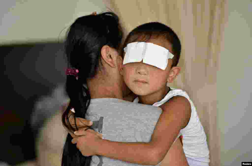 A six-year-old boy, whose eyes were gouged out, is held by his mother at a hospital in Taiyuan, Shanxi province. Chinese police suspect the boy's aunt of gouging out his eyes, Xinhua state news agency said, the latest twist in the investigation of a crime that shocked the country.