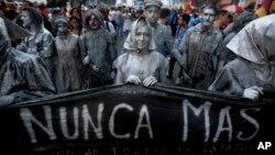 """Las actrices que representan a las madres de la Plaza de Mayo, tienen una pancarta que lee en español: """"nunca más"""", durante una marcha marcando el 41 aniversario del golpe militar en Buenos Aires, Argentina, el viernes 24 de marzo de 2017."""