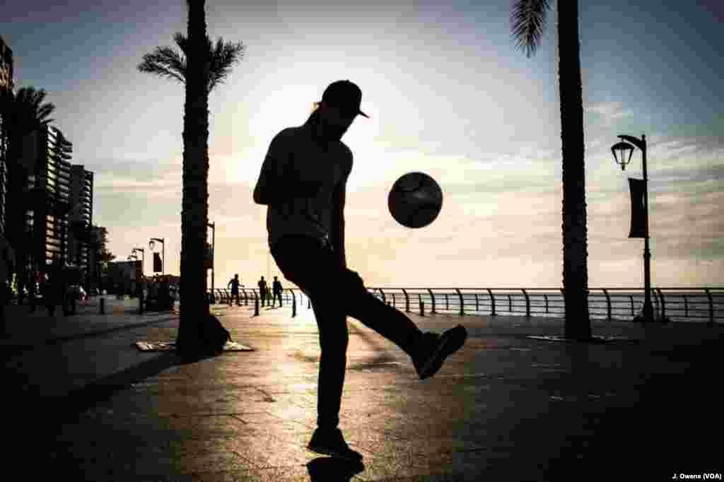 Seorang anak muda bermain sepakbola di pinggir laut Beirut.