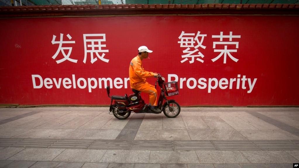 在北京市中心,清洁工骑车经过中英文标语牌(2015年7月15日)