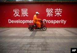 清洁工骑车经过标语牌(2015年7月15日)