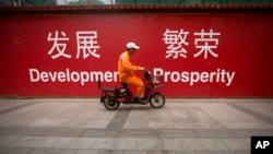 "FILE - A maintenance worker rides a scooter past banners reading ""Development"" and ""Prosperity"" in English and Chinese on a street in central Beijing, July 15, 2015. An estimated $1 trillion dollars are needed to underpin Asia's growth."