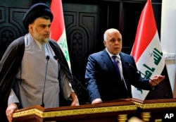 FILE - In this photo provided by the Iraqi government, Iraqi Prime Minister Haider al-Abadi, right, and Shiite cleric Muqtada al-Sadr hold a press conference in the heavily fortified Green Zone in Baghdad, Iraq, May 20, 2018.