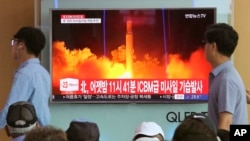 FILE - In this July 29, 2017 photo, People watch a TV news program showing an image of North Korea's latest test launch of an intercontinental ballistic missile (ICBM), at the Seoul Railway Station in Seoul, South Korea.
