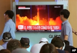 FILE - In this July 29, 2017 photo, People watch a TV news program showing an image of a North Korea test launch of an intercontinental ballistic missile, at the Seoul Railway Station in South Korea.