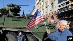 Un polaco saluda al convoy de vehículos blindados de la OTAN durante una parada en la plaza central en Bialystok en Polonia.