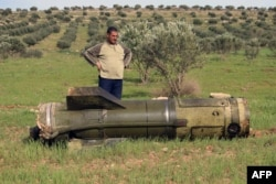A Syrian man stands next to an unexploded ground-to-ground missile, fired by government forces on the southern Syrian city of Daraa on March 27, 2017.