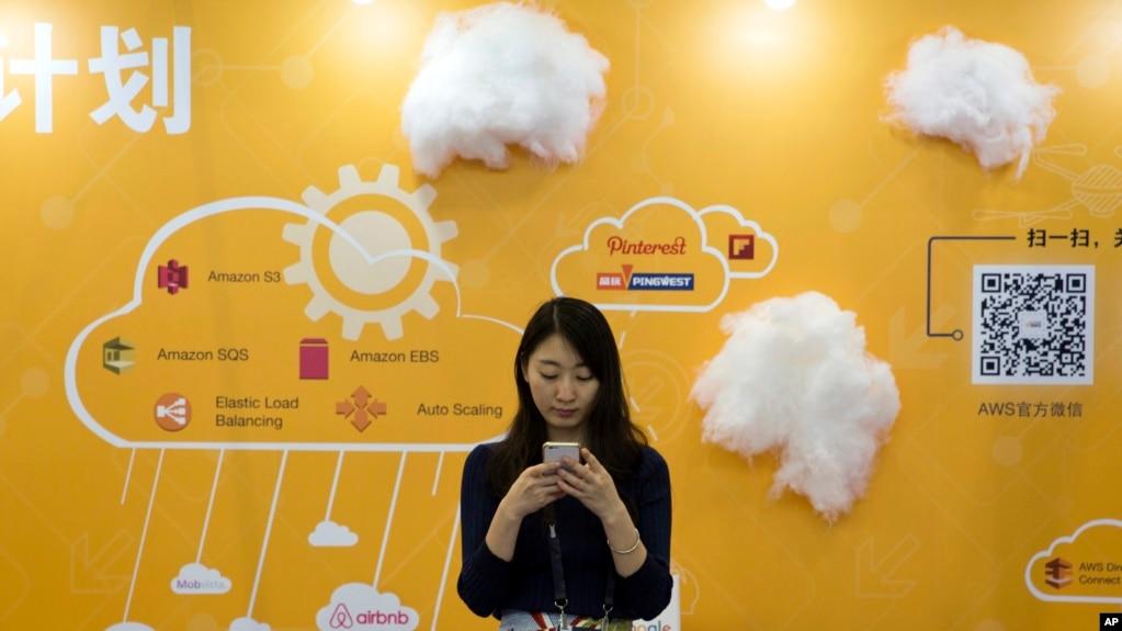 在北京的全球移動互聯網大會上,一位女士在推廣云服務的攤位前使用手機(2016年4月29日)