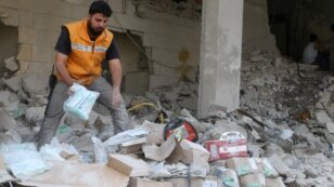 A Red Crescent aid worker inspects scattered medical supplies after an airstrike on a medical depot in the rebel-held Tariq al-Bab neighborhood of Aleppo, Syria, April 30, 2016.