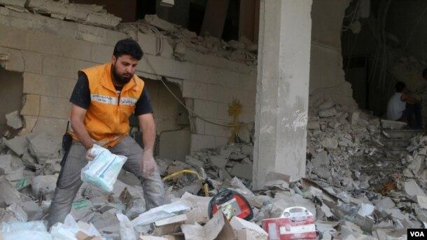 Beynəlxalq Qızıl Aypara Cəmiyyətinin işçisi Hələbdə hava hücumlarından sonra dağıntılar arasında