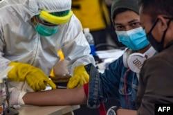 Para petugas kesehatan melakukan pemeriksaan kesehatan 156 pekerja migran Indonesia yang tiba dari Malaysia di Bandara Juanda, Surabaya, 7 April 2020. (Foto: AFP)