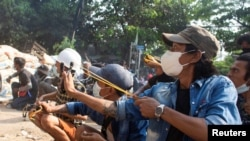 Protesters use slingshots while taking cover behind a barricade as smoke rises from burning debris during ongoing protests against the military coup, in Monywa, Sagaing region, Myanmar March 29, 2021 in this still image from video obtained by REUTERS AT