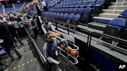 Seorang petugas memberesi bola-bola basket setelah laga bola basket antar universitas NCAA, Atlantic Coast Conference, dibatalkan, Greensboro, N.C., 12 Maret 2020.