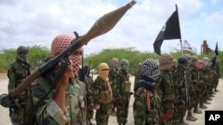 Al-Shabab fighters display weapons as they conduct military exercises in northern Mogadishu, Somalia, Oct. 21, 2010 file photo.