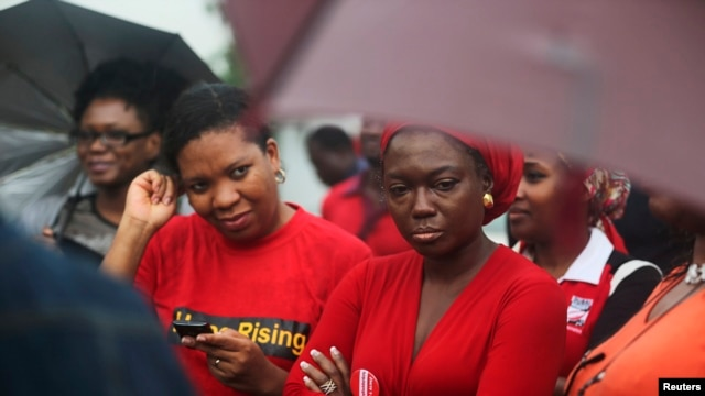 "FILE - Activists attend a ""Bring Back Our Girls"" rally to pressure Nigeria's government to find schoolgirls abducted in April, Lagos, July 5, 2014."