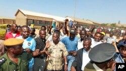 """Le candidat d'opposition Michael """"King Cobra"""" Sata (au centre), sort d'un bureau de vote à Lusaka, le mardi 20 septembre 2011"""