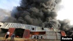 Para petugas pemadam kebakaran berupaya memadamkan api yang membakar gudang Program Pangan Dunia PBB di Hodeida, Yaman, 31 Maret 2018. (Foto: dok).