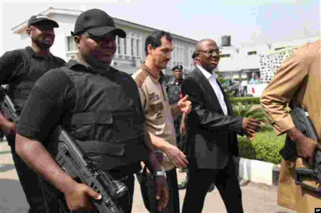 Iranian Azim Aghajani, center, charge with orchestrating an illegal arms shipment into Nigeria that contained mortars and military-grade weapons, is escorted after the start of his trial, at the Federal High Court in Lagos, Nigeria ,Wednesday, Feb. 16, 20