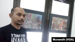 Pelukis dan aktivis Andreas Iswinarto di depan lukisan abstrak yang terinspirasi perjuangan almarhum aktivis Wiji Thukul yang dipamerkan di PUSHAM UII, Banguntapan Bantul Yogyakarta (Foto: Munarsih)