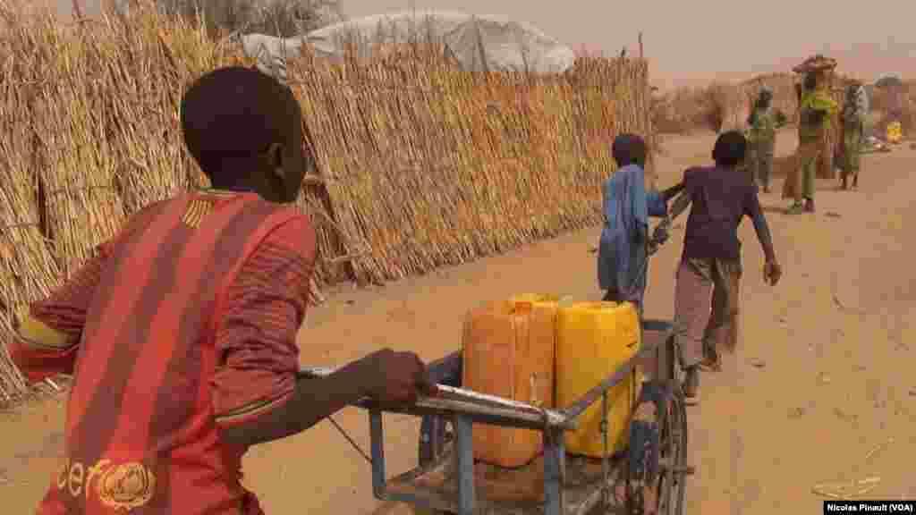 Des enfants apportent de l'eau dans le camp de réfugiés d'Assaga, Diffa, Niger, le 17 avril 2017 (VOA/Nicolas Pinault)