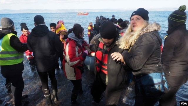 Volunteers and aid workers help refugees get to shore after they landed on the northern part of the island of Lesbos, Greece, Jan. 20, 2016. (H. Elrasam/VOA)