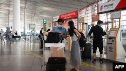 တရုတ္ႏိုင္ငံ Beijing ၿမိဳ႕ရဲ႕ အျပည္ျပည္ဆိုင္ရာ ေလဆိပ္မွာ ခရီးသြားတခ်ိဳ႕ ေလယာဥ္ပ်ံလက္မွတ္ကို စစ္ေဆးေနၾကတဲ့ ျမင္ကြင္း။ (ဇြန္ ၁၇၊ ၂၀၂၀)