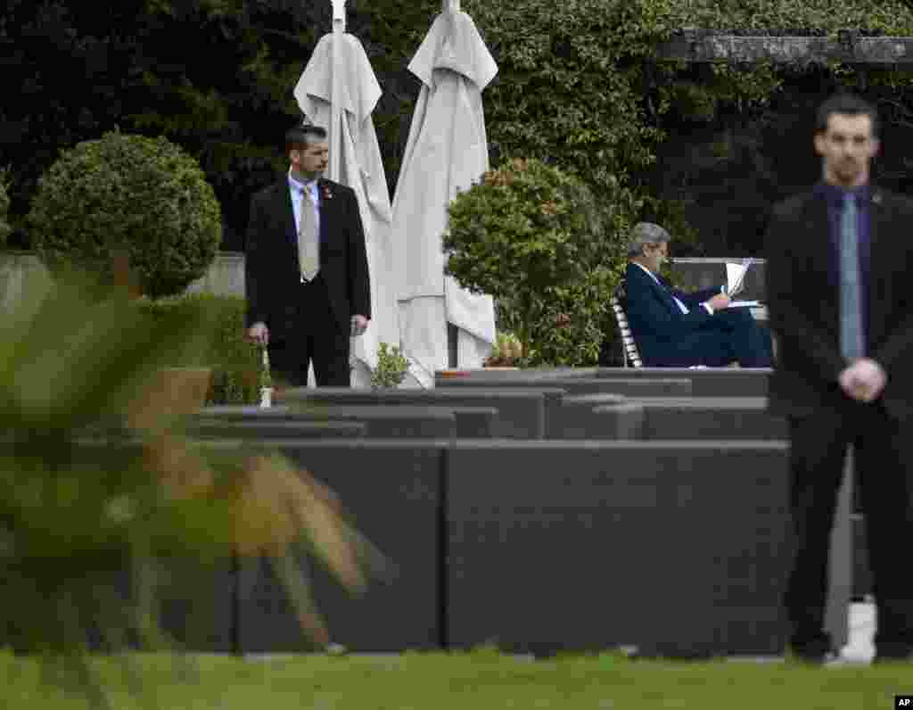 U.S. Secretary of State John Kerry looks over papers in the courtyard of the Beau Rivage Palace Hotel after an extended round of talks on Iran's nuclear program, in Lausanne, April 2, 2015.