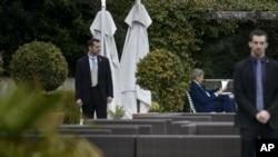 Le Secrétaire d'Etat américain John Kerry, centre droit, épulche des documents dans une cour, au Beau Rivage Palace Hôtel, au cours d'une ronde d'extension des pourparlers sur le programme nucléaire de l'Iran, le jeudi 2 Avril 2015 à Lausanne, Suisse.