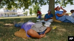 Roofers take their lunch break in the shade of a tree in rural Ashland, Nebraska, Aug. 27, 2013, as a late summer heat wave sends temperatures into the high 90s.