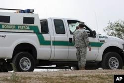 In this April 19, 2011 photo, a National Guardman talks with U.S. Border Patrol agents stationed along the Hidalgo International Bridge in Hidalgo, Texas.