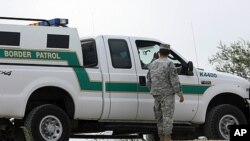 In this April 19, 2011 photo, a National Guardman talks with U.S. Border Patrol agents stationed along the Hidalgo International Bridge in Hidalgo, Texas