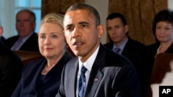 FILE - This Nov. 28, 2012, file photo shows then-secretary of state Hillary Rodham Clinton listening as President Barack Obama speaks in the Cabinet Room at the White House in Washington.