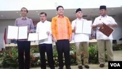 Ketua KPU Husni Kamil Manik (tengah) bersama pasangan Capres-Cawapres Joko Widodo dan Jusuf Kalla (kiri) dan Prabowo Subianto-Hatta Rajasa dalam pengumuman laporan kekayaan di Jakarta, Selasa (1/7).