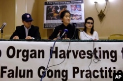 FILE - Dr. Wenyi Wang (C) holds a press conference with others, who preferred not to be identified, in Arlington, Virginia, April 26, 2006, about her having interrupted Chinese President Hu during his speech at the White House in Washington. Wang said she interrupted Hu to bring global attention to the organ harvesting from living Falun Gong practitioners in China.