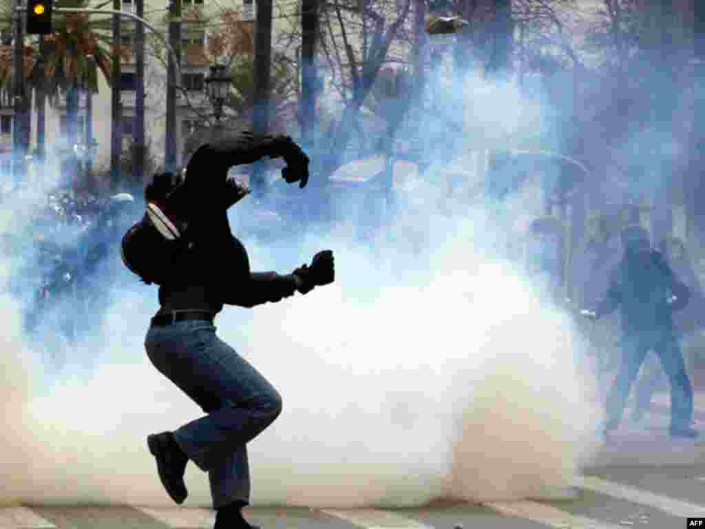 A protester throws a stone toward riot police during clashes during a two-day general strike against planned austerity measures in Athens, February 10, 2012. (AP)