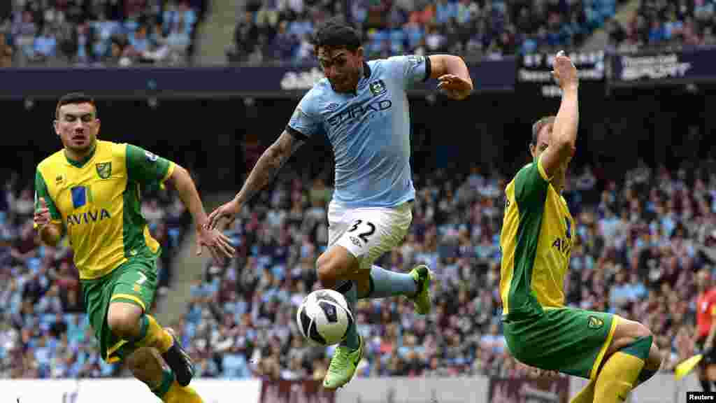 Norwich City's Steven Whittaker (R) and Robert Snodgrass (L) challenge Manchester City's Carlos Tevez (C) during their English Premier League soccer match in Manchester, May 19, 2013.