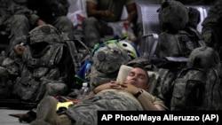 資料照片:美國陸軍第三裝甲團的軍人在巴格達薩瑟空軍基地客運航站內小憩。 (2011年8月2日)