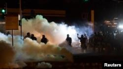 Polisi anti huru-hara membubarkan demonstran di Ferguson, Missouri (13/8).