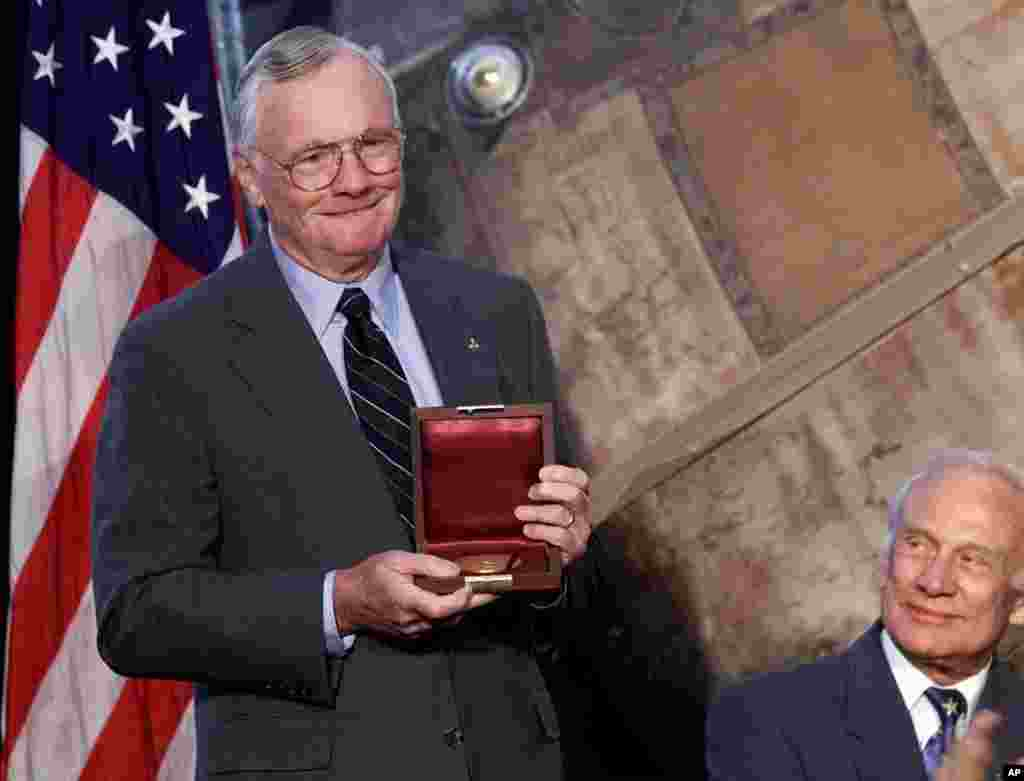 Apollo 11 astronaut, and the first man to walk the moon, Neil Armstrong, left, holds the Langley Gold Medal after it was presented to him by Vice President Al Gore at a ceremony at the Smithsonian Air And Space Museum in Washington, July 20, 1999.