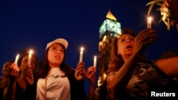 FILE - People attend a candlelight vigil for people missing after a boat carrying migrants from Tunisia sank off the southern Italian island of Lampedusa, September 2012, in Tunis September 10, 2012.