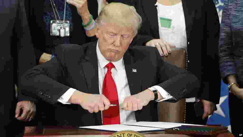 Le président Donald Trump signe un décret pour construire le mur frontalier au département de sécurité à Washington, le 25 janvier 2017.